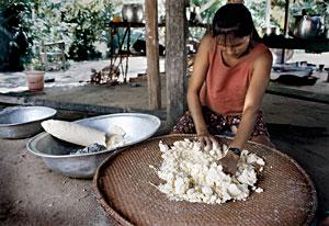 mulher  preparando a farinha de mandioca